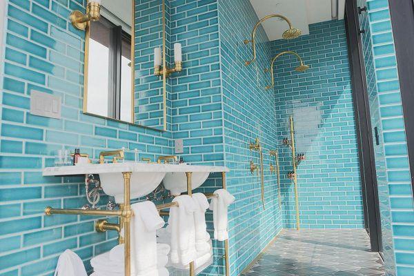 Không gian phòng tắm trở nên sang trọng và đẳng cấp hơn với sự kết hợp giữa đồ nội thất màu vàng đồng và mẫu gạch thẻ màu xanh độc đáo